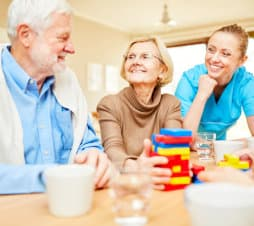 senior couple with their caregiver playing table toy