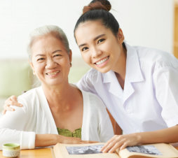 caregiver and senior woman smiling while reading a book