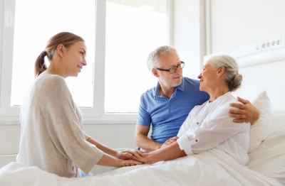 senior couple with a caregiver talking